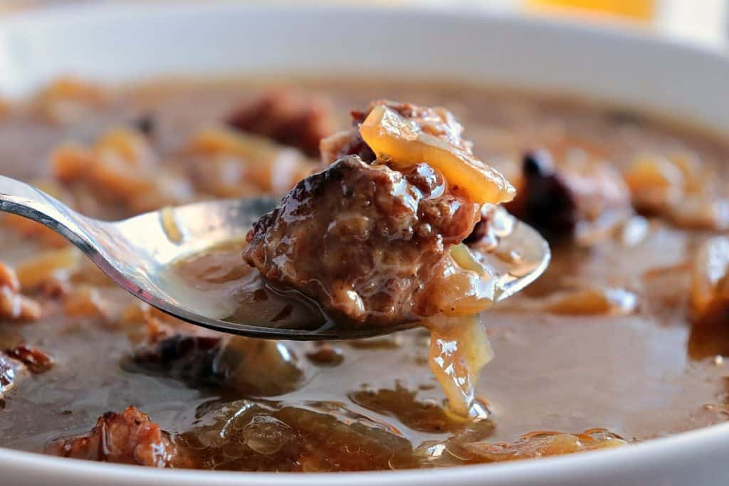 Closeup of a spoonful of German Soup with German Sausage and onions.