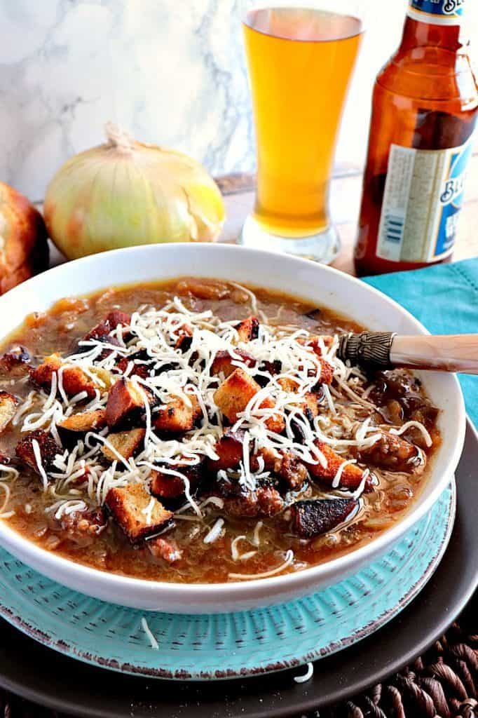 A bowl of German onion soup with a spoon, pretzel croutons and shredded cheese. A beer and onions are in the background.