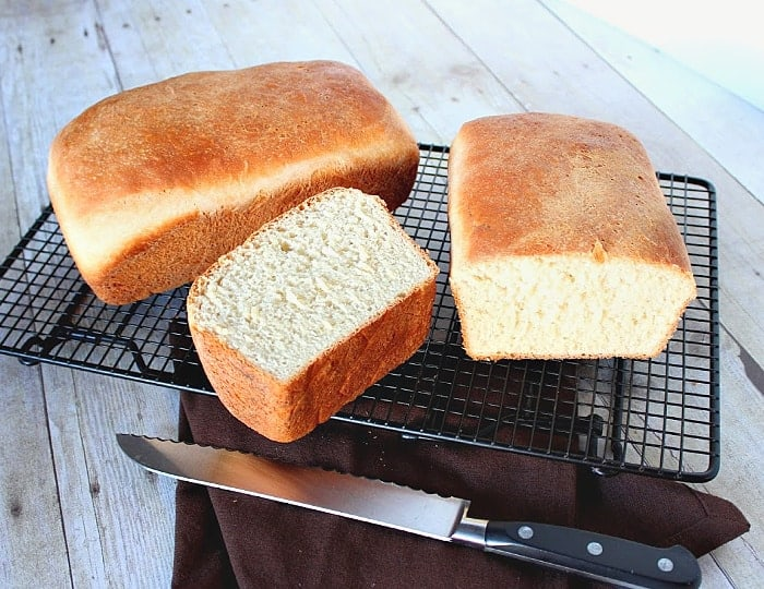 A horizontal photo of two loaves of buttermilk honey bread on a cooling rack with a serrated knife.