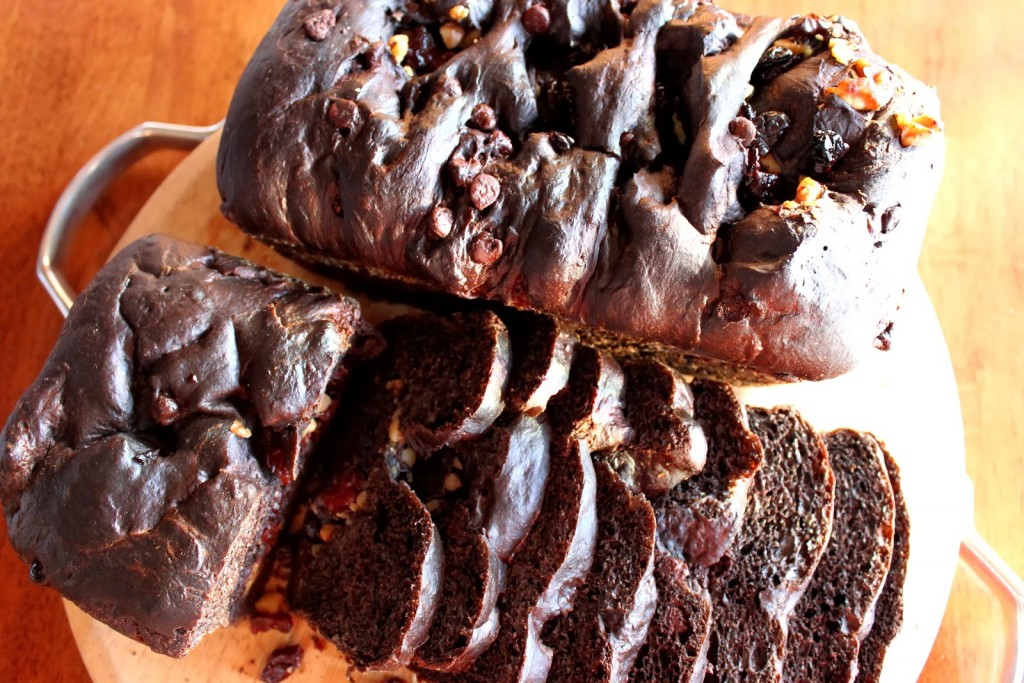 Overhead photo of a slice chocolate cherry yeast bread on a wooden cutting board