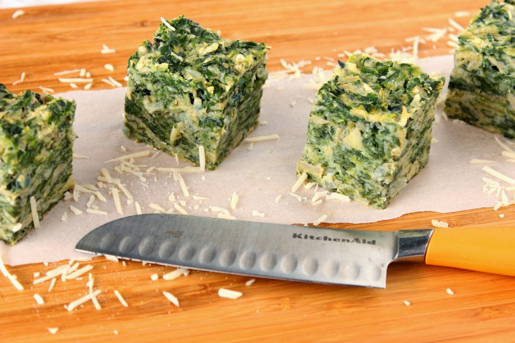 4 square of spinach artichoke appetizers on a cutting board with a knife