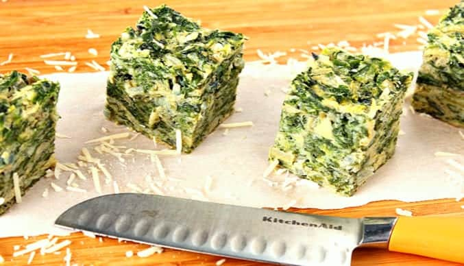 Square of Artichoke and Spinach on a wooden cutting board with shredded Parmesan cheese and a knife. bbq side dish roundup