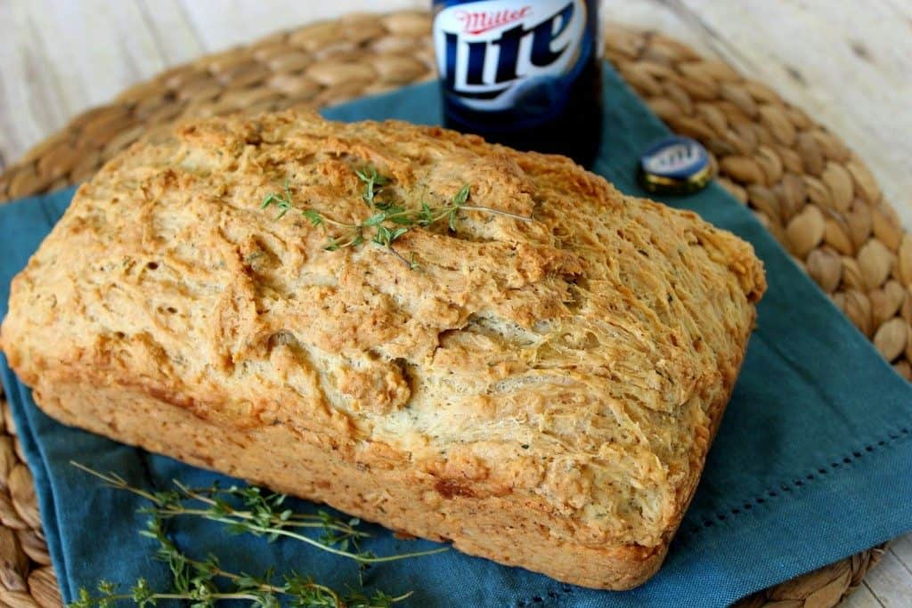 Loaf of beer bread with a bottle of beer in the background.