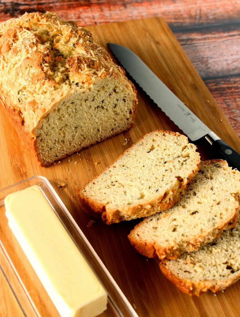 Slices of Homemade Soda Bread on a cutting board with a serrated knife and a stick of butter.
