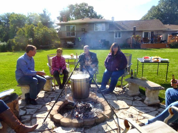 People sitting around a firepit as a low country boil is cooking in a giant pot.