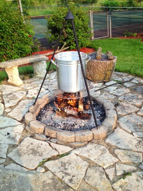 A large pot and a firepit tripod outside for cooking a low-country seafood boil.