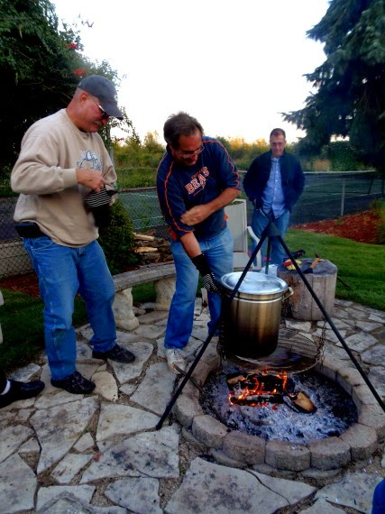 People cooking a low country boil over a firepit.