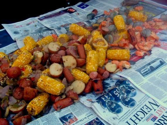 A low country boil seafood and sausage feast spilled out onto a newspaper lined table.
