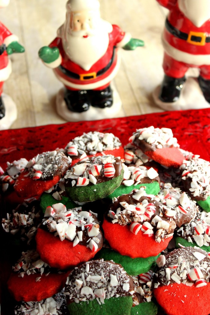 Vertical photo of red and green cookies dipped in chocolate with peppermint candy and Santa in the background.
