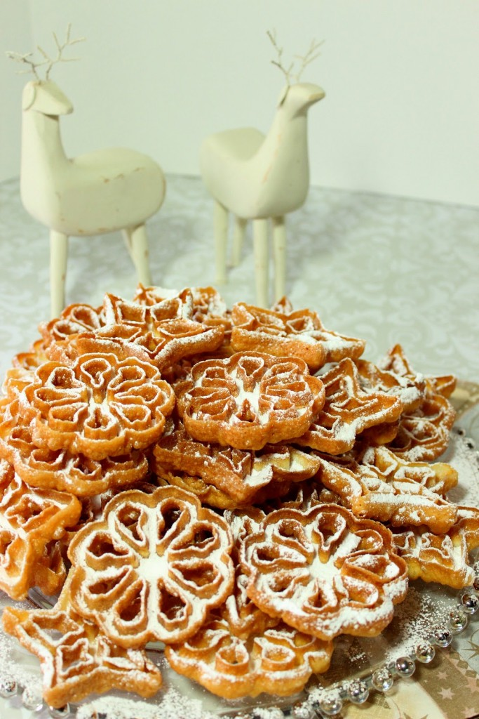 A vertical photo of a glass plate loaded with fried rosette snowflake cookies with confectioner sugar dusting.