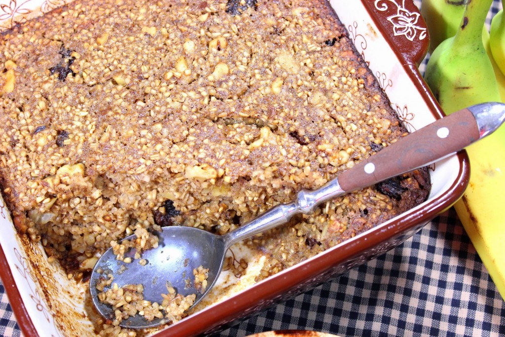 Overhead picture of baked steel cut oatmeal in a baking dish with a spoon.