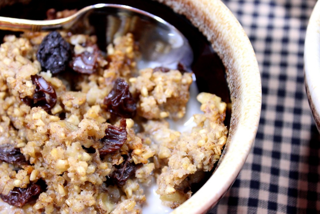 Closeup picture of baked steel cut oatmeal with raisins in a brown bowl.