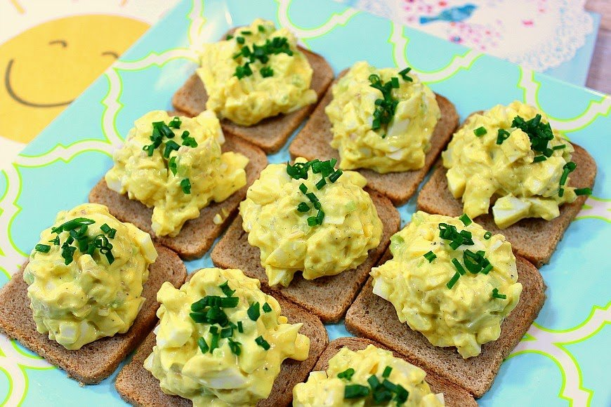 Closeup picture of egg salad on 9 squares of party bread.