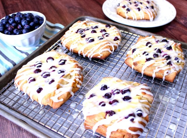 A baking sheet with a rack and 4 blueberry cheese Danish.