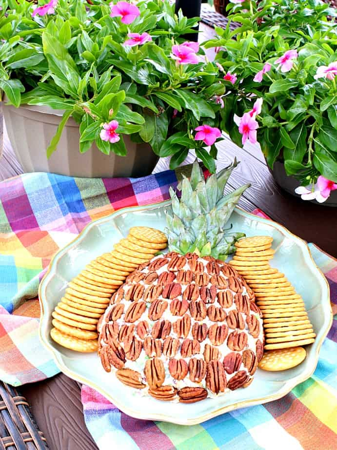 Vertical image of a pineapple cheese ball on a platter with crackers and colorful napkins