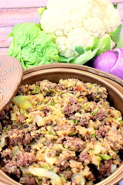 Low Carb Unstuffed Cabbage Casserole in a tan casserole dish with cauliflower, red onion, and cabbage accents.
