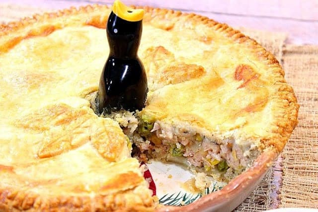 A closeup horizontal photo of a pork pot pie with a slice taken out and a pie bird in the center.