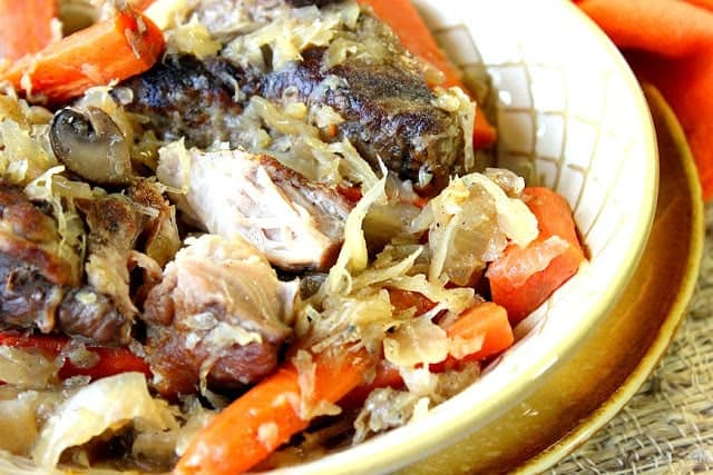 Closeup photo of a bowl of German Pork Ribs and Sauerkraut with carrots and mushrooms