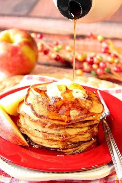 A stack of apple cider pancakes with syrup being poured down on them.