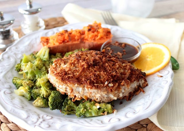 Colorful dinner of Tuna steak crusted with coconut on a white scalloped plate with broccoli, sweet potato and dipping sauce.