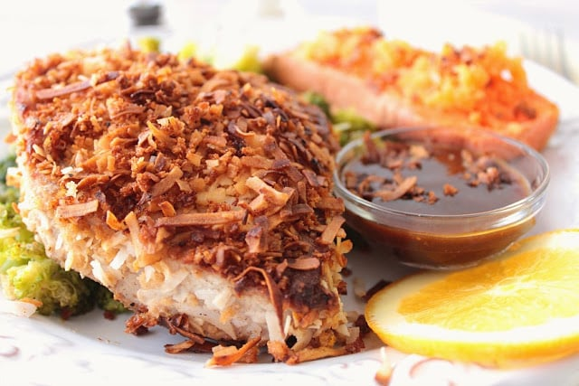 Closeup picture of a coconut crusted tuna steak with dipping sauce on a white plate