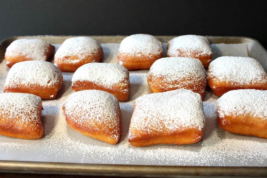 Powdered sugar beignets on a baking sheet