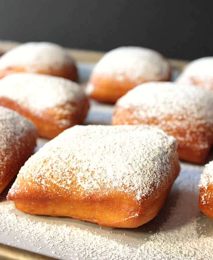 Closeup picture of a square beignet with powdered sugar dusting.