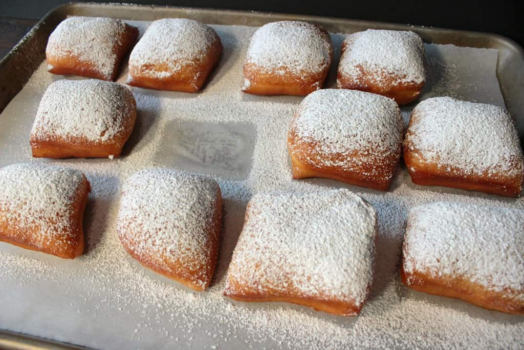 Confectioners sugar dusted beignets on a baking sheet with parchment paper.