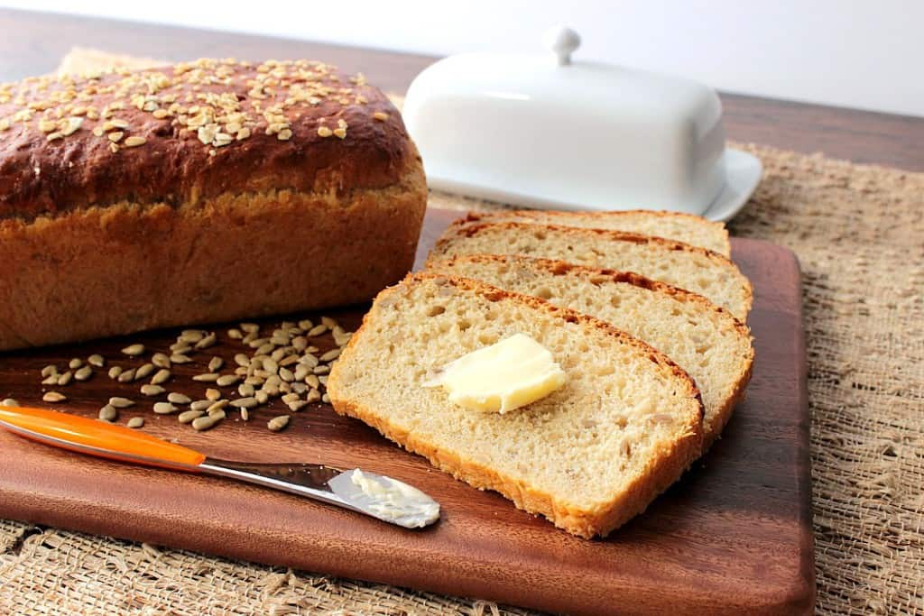 A horizontal photo of a loaf of oatmeal honey bread on a cutting board with a knife, butter dish, and a pat of butter.