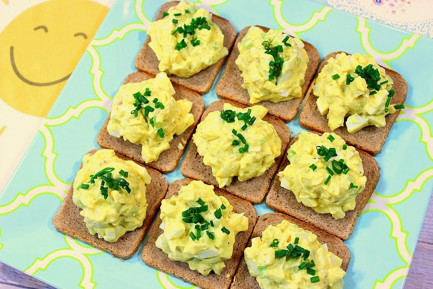 Egg Salad on cocktail bread on a square plate.