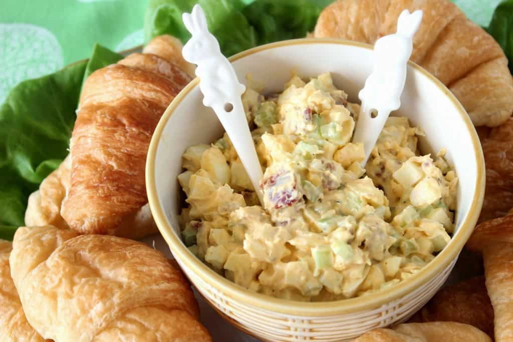 Egg salad in a bowl with croissants and bunny spoons.