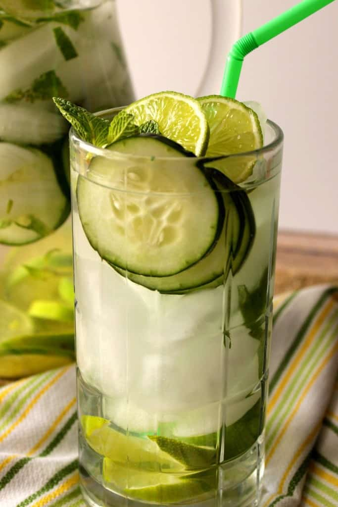A vertical closeup photo of cucumber lime fitness water in a glass with ice and mint.