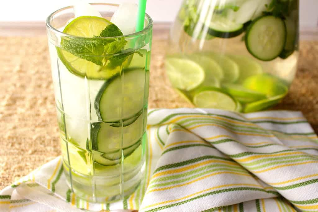 A horizontal photo of a glass of hydrating fitness water with sliced limes, cucumbers, and mint with ice and a green and yellow cloth napkin.