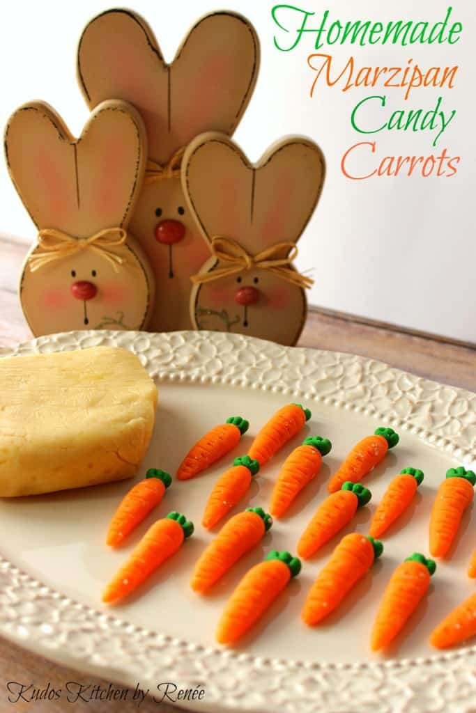 Homemade Marzipan Candy Carrots on a white plate along with a block of homemade marzipan with bunnies in the background.