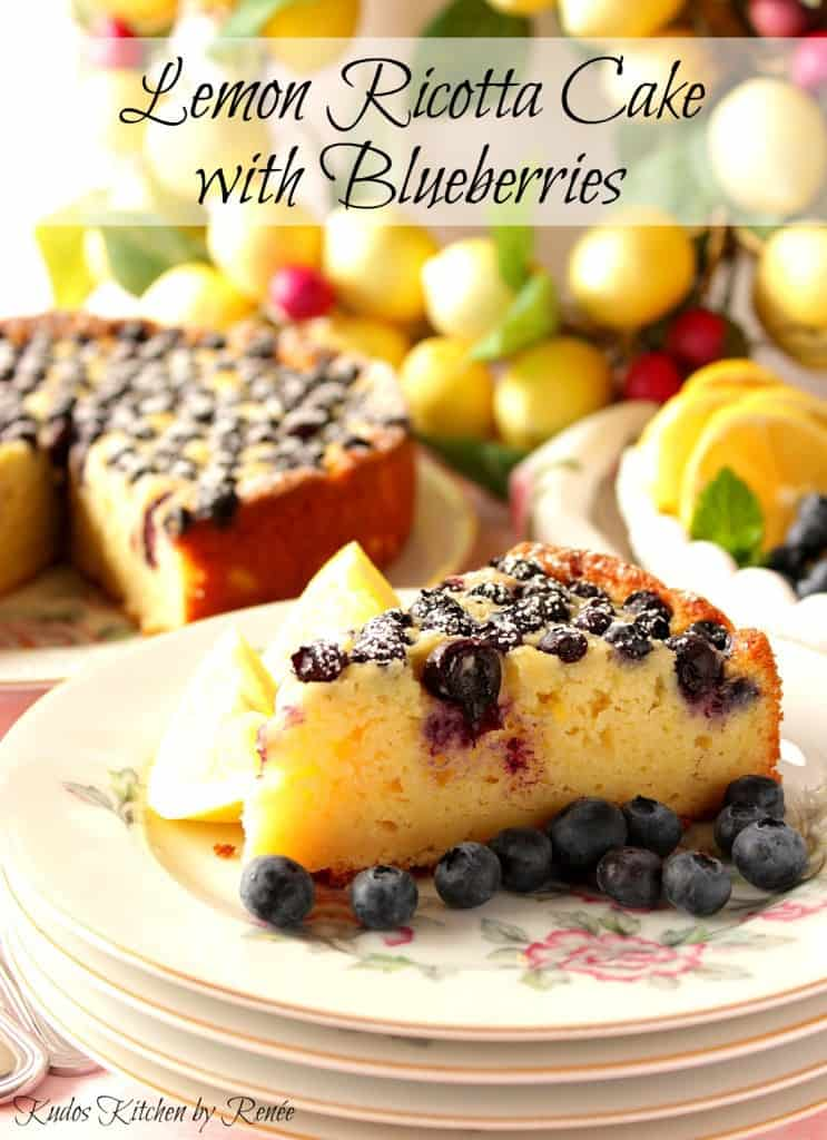 A beautiful slice of lemon ricotta cake on a pretty plate with fresh blueberries.