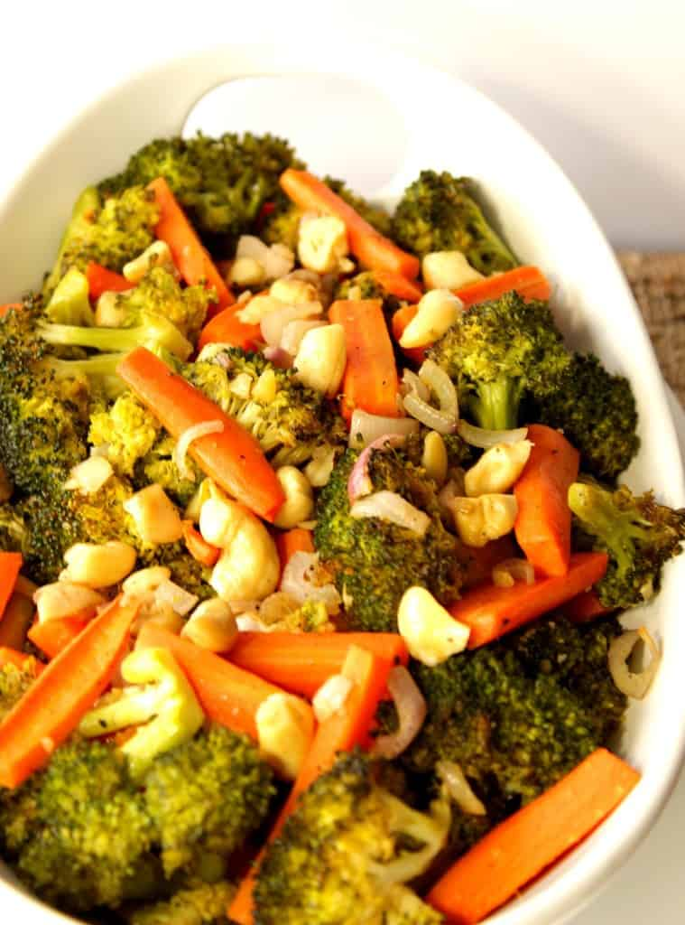 Vertical image of broccoli and carrots in a white bowl.