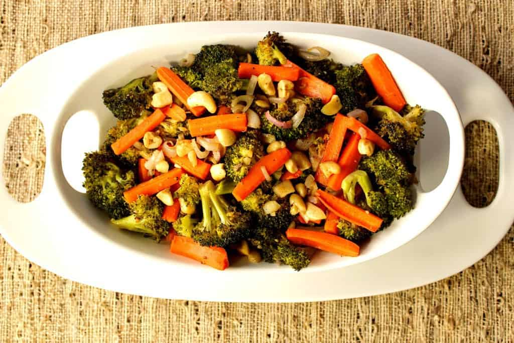 Overhead photo of carrots and broccoli in a white bowl on a white platter on a tan colored tablecloth.