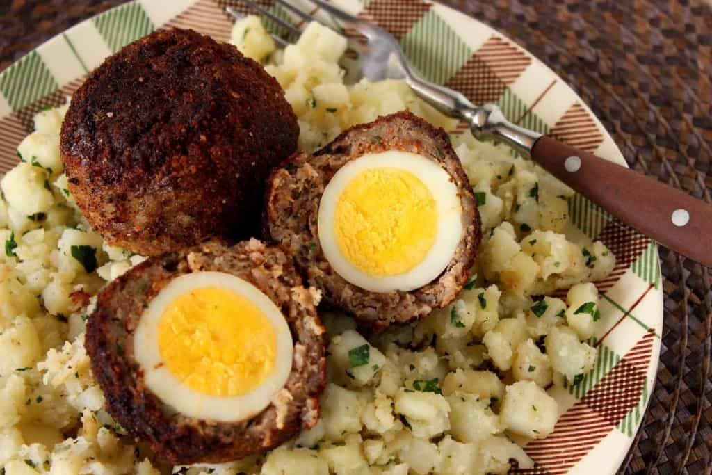 Scotch Eggs wrapped in sausage on a plaid plate.