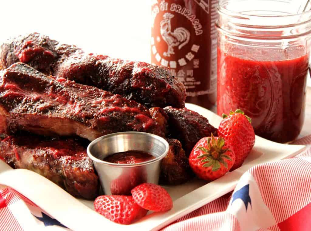 A horizontal photo of a pile of pork ribs on a white plate the strawberries and bbq sauce.