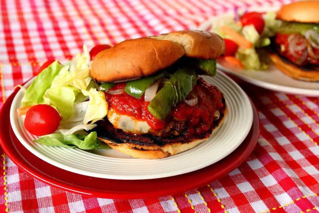 Italian Sausage Pizza Burger with Peppers on a red and white table cloth.