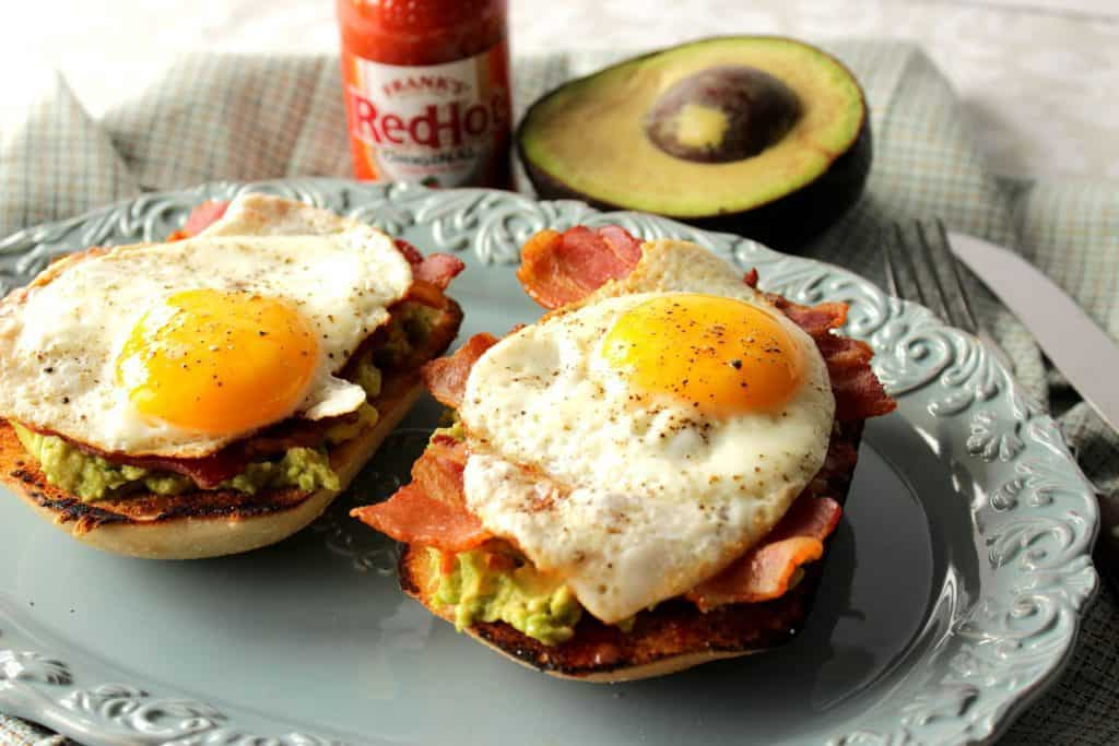 A horizontal photo of two avocado toast breakfast sandwiches on a blue plate with sunny side up eggs and bacon.