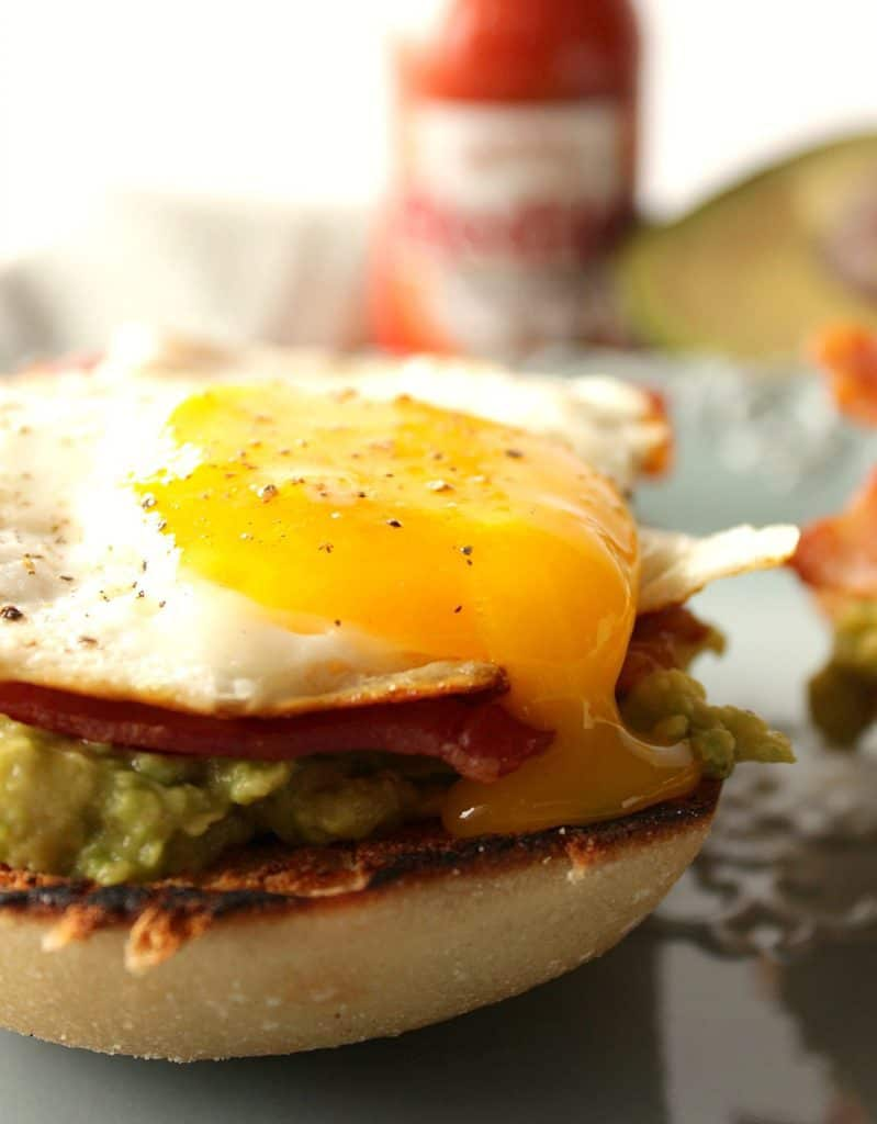 A closeup vertical photo of a runny yolk egg on an avocado toast breakfast sandwich with bacon.