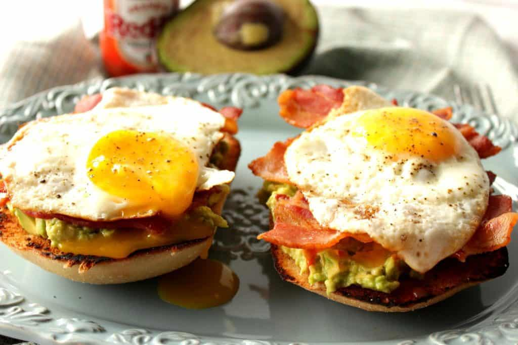 Two avocado toast with bacon and egg breakfast sandwiches on a blue plate with an avocado half and hot sauce in the background.