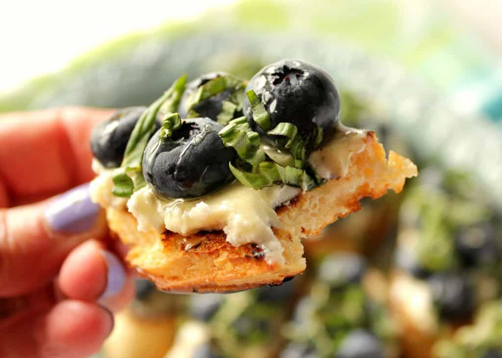 A closeup photo of a hand holding a blueberry basil bruschetta with a bite taken out.