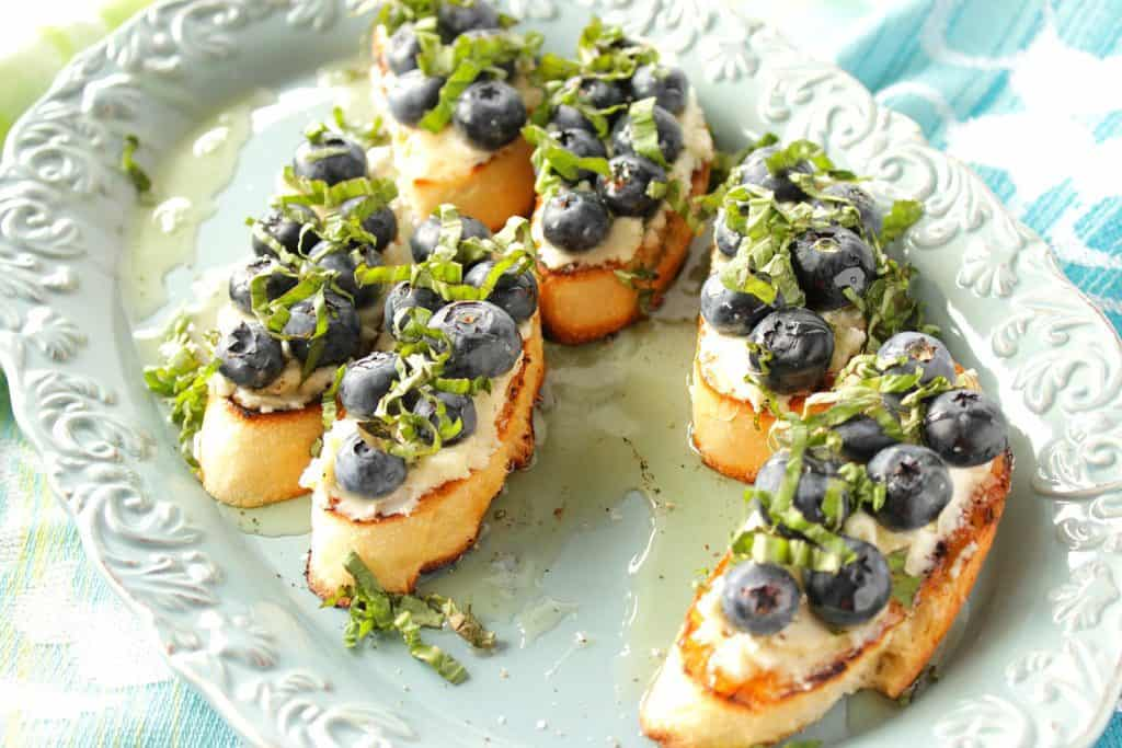 Blueberry, goat cheese, and basil bruschetta appetizer.