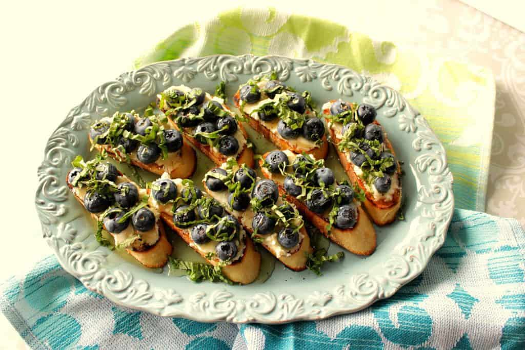 On overhead photo of a plate of goat cheese and blueberry basil brushchetta with a blue napkin