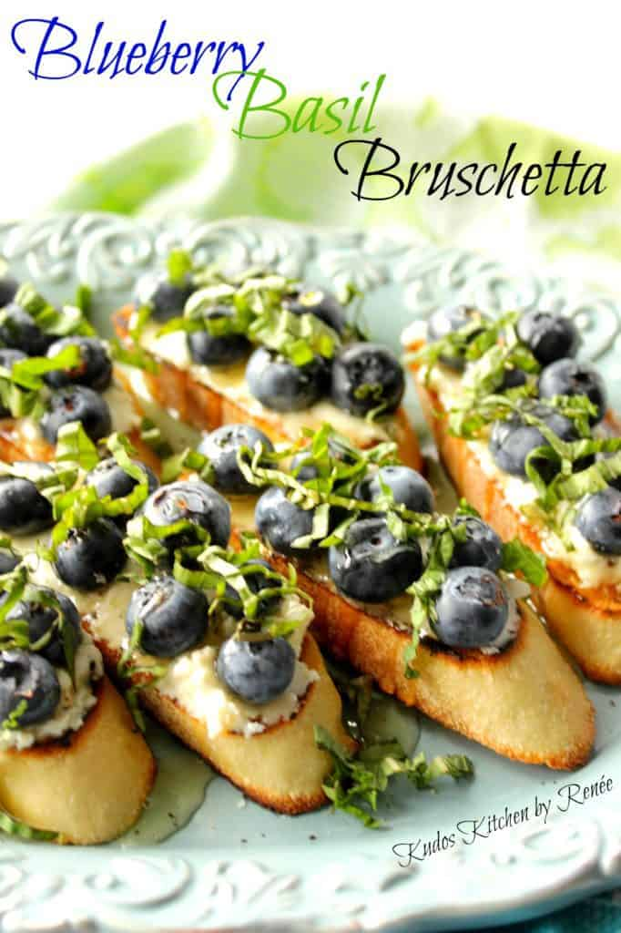 A closeup vertical photo of a bunch of blueberry basil bruschetta appetizers with a title text overlay graphic