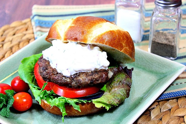 Lamb and Feta Burgers with Tzatziki Sauce on a green square plate.