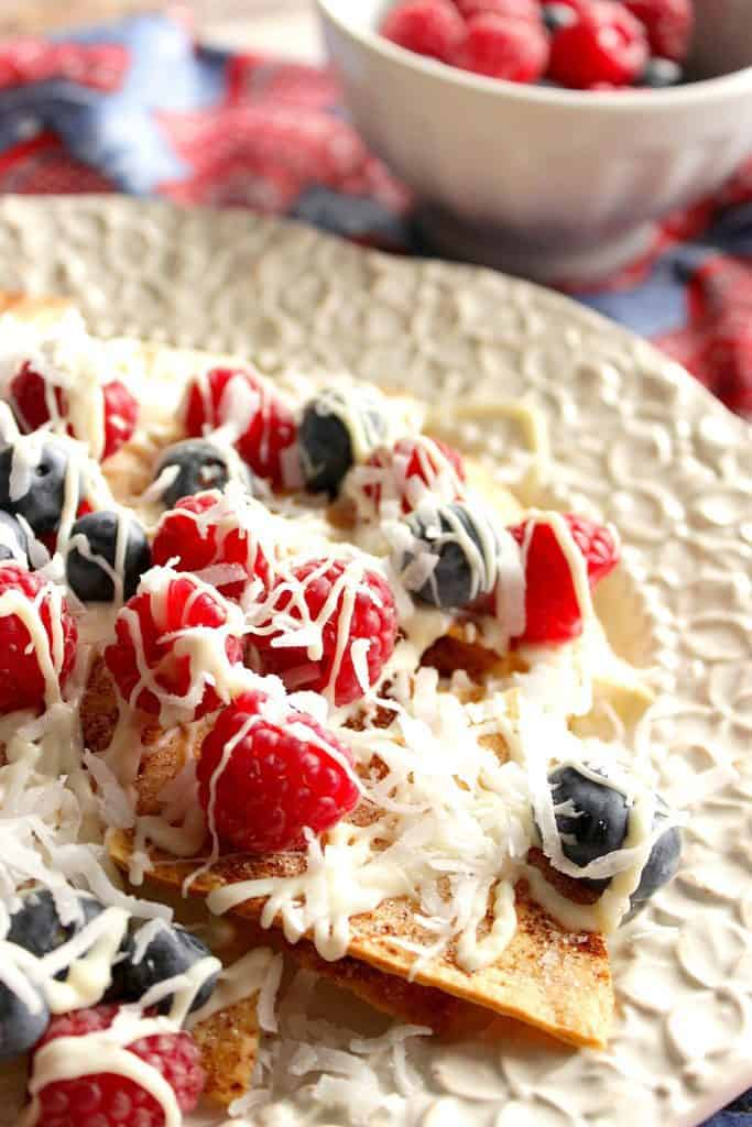 Vertical closeup image of crispy cinnamon sugar dessert nachos with red and blue berries and a white chocolate and coconut drizzle.