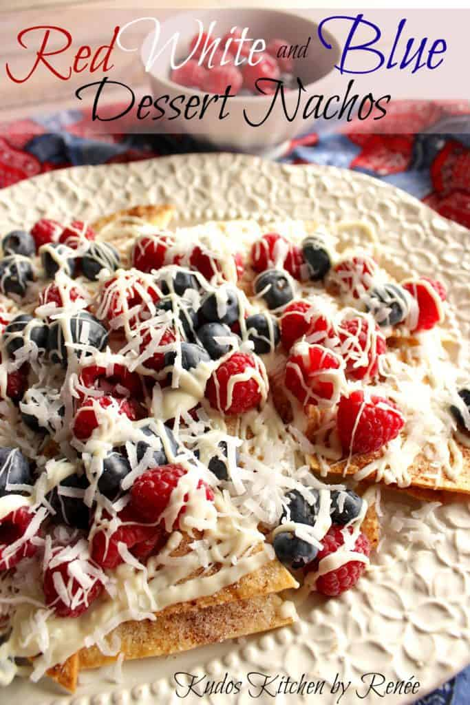 Closeup vertical image of cinnamon sugar dessert nachos topped with berries and white chocolate.